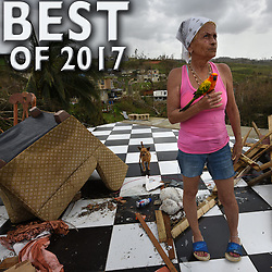 September 27, 2017 - Corozal, Puerto Rico - IRMA MALDANADO holds her bird Sussury as she looks at what's left of her devastated home after hurricane Maria ravaged the island. (Credit Image: © Carol Guzy via ZUMA Wire)