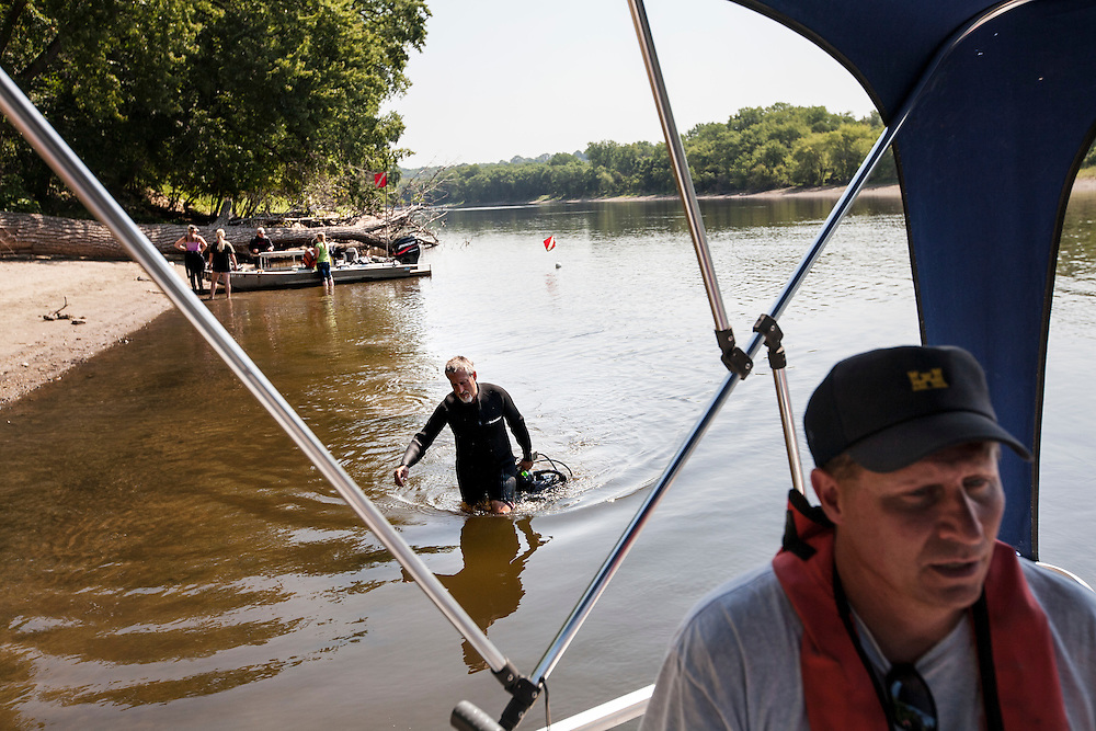 Byron Karns, center, an aquatic biologist with the National Park Service, returns to a boat after diving for mussels in the Mississippi River near Pike Island August 14, 2015. Dan Kelner, right, with the U.S. Army Corps of Engineers is also part of this inter-agency effort to assess the health of all mussel species in the river.