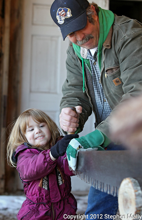 Makayla Kroeger (from left), of Cedar Falls, participates in the Cross Cut Log Sawing Competition with some help from Amana Society Forester Larry Gnewikow during Winterfest at the Market Barn in Amana on Saturday, January 28, 2012. Activities included the Best Beard Competition, winter wreath toss, the Great Amana Ham-Put, hammerschlagen, and a log sawing competition. (Stephen Mally/Freelance)