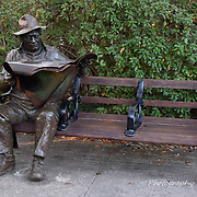 Bronze Sculpture of Man sitting on park bench reading newspaper.