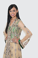 Portrait of an Indian woman in designer wear standing with hands on hips over gray background