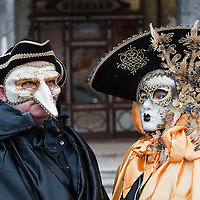 VENICE, ITALY - FEBRUARY 20:  A couple wearing Carnival costumes and masks pose in St Mark Square on February 20, 2011 in Venice, Italy. The Venice Carnival, one ofthe largest and most important in Italy, attracts thousands of people from around the world each year. The theme for this year's carnival is Ottocento amd Sissi, a nineteenth century evocation, andwill runfrom February 19 till March 8.
