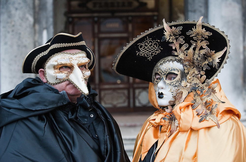 VENICE, ITALY - FEBRUARY 20:   A couple wearing Carnival costumes and masks pose in St Mark Square on February 20, 2011 in Venice, Italy. The Venice Carnival, one of the largest and most important in Italy, attracts thousands of people from around the world each year. The  theme for this year's carnival is Ottocento amd Sissi, a nineteenth century evocation, and will run from February 19 till March 8.