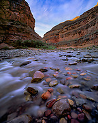 The San Juan river cascades over colorful rocks that line the river bottom near John's Canyon, Utah.
