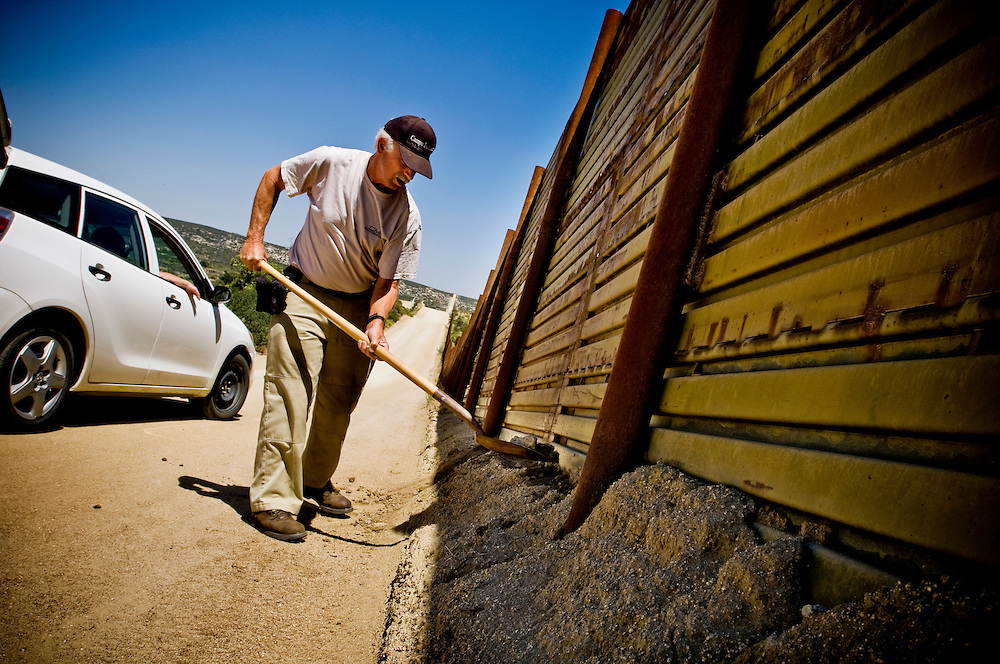 "Greyhound trip..Minuteman ""Gadget Dan"" repairing a hole dug under the border wall by crossing Mexican immigrants...Photographer: Chris Maluszynski /MOMENT"