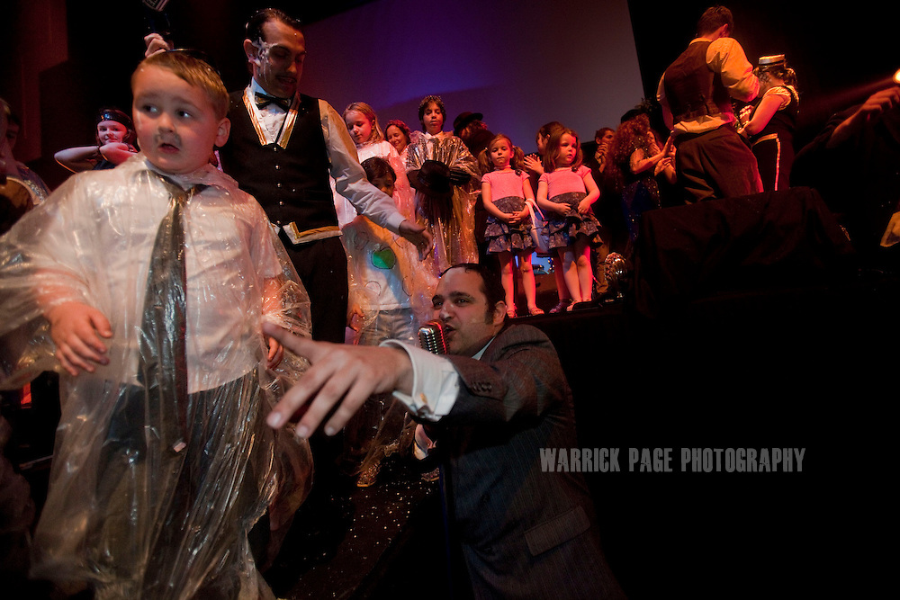 LONDON, ENGLAND - MARCH 24: Children and parents participate in the finale of Future Cinema's matinee performance/screening of Bugsy Malone on March 24, 2012, in London, England. Future Cinema is a live production aimed at bring back the 'experience' of film, by combining both scripted and improvised performances to accompany the screening of classic and pop-culture movies at different venues around London. Audience members are encouraged to dress in costume and are regularly incorporated into the production. (Photo by Warrick Page)