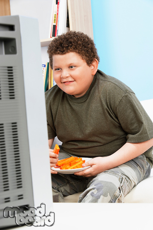 Overweight Boy (13-15) Eating Carrot Sticks in Front of Television