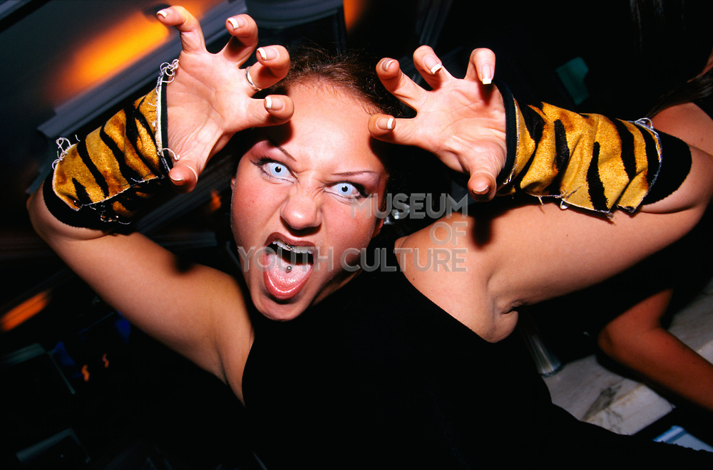 Girl in a club wearing tiger cuffs blue contact lenses with mouth piercings. Ibiza 2000
