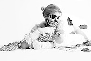 female lying down with skeleton makeup holding skeleton shot in black and white on white background