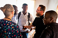 The Rev. Daniel Mulholland, pastor of Shepherd of the Valley Lutheran Church, Fort Bridger, Wyo., greets local evangelists and pastors on the first day of the LCMS Mercy Medical Team on Monday, May 7, 2018, in the Yardu village outside Koidu, Sierra Leone, West Africa. LCMS Communications/Erik M. Lunsford