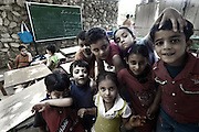 "A.P.E.,NGO School  in Mokattam.On the outskirts of Cairo in the middle of Manshiet Nasr neighborhood is located Mokattam settlement known as ""Garbage City"" is inhabited by Zabbaleen, a community of about 45,000 Coptic Christians living for decades to recycle waste generated by the Egyptian capital: plastic, aluminum, paper and organic waste transformed into compost. Most part of the Association for the Protection of the Environment (APE), an NGO that works in the area, whose objectives are to protect the environment and improve the livelihoods of garbage scavengers in Cairo. According to the UN, the work is done in Mokattam is one of the ten best examples of world environmental improvement. El Cairo , Egipt, June 2011. ( Photo by  Jordi Camí )."