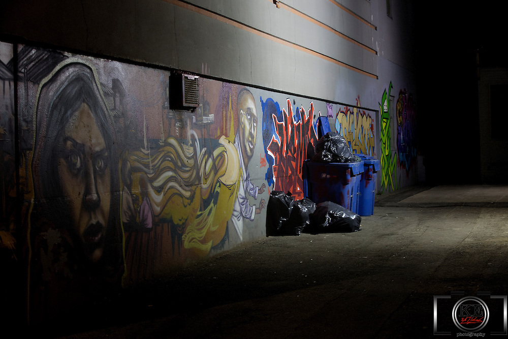 Garbage collected in front of a beautiful graffiti wall lit by a street lamp, in an alley way at nighttime.