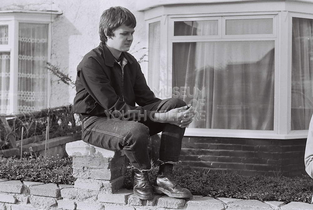 Teenager in frayed jeans and Harrington jacket sitting on a brick wall, London, Greenford, UK 1980.