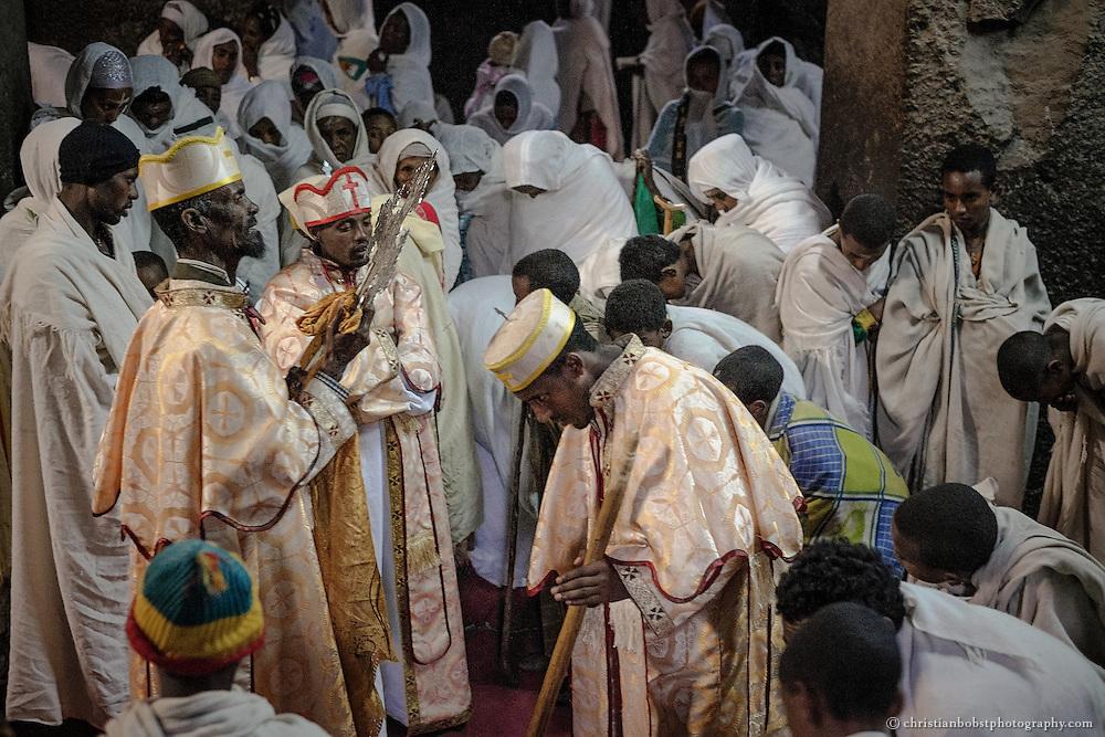 Ein Priester wird durch einen höheren Geistlichen mit einem Prozessionskreuz gesegnet.