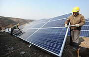 YANTAI, CHINA - NOVEMBER 17: (CHINA OUT) <br /> <br /> Terrestrial Photovoltaic Power Project Built<br /> <br /> A worker installs polycrystalline silicon solar panels as terrestrial photovoltaic power project starts in Guanshui Town of Muping District on November 17, 2015 in Yantai, Shandong Province of China. The project covering more than 300 arces of barren hills began in July and was expected to completed by end of the year, with a total installed capacity of 40 megawatts.<br /> ©Exclusivepix Media