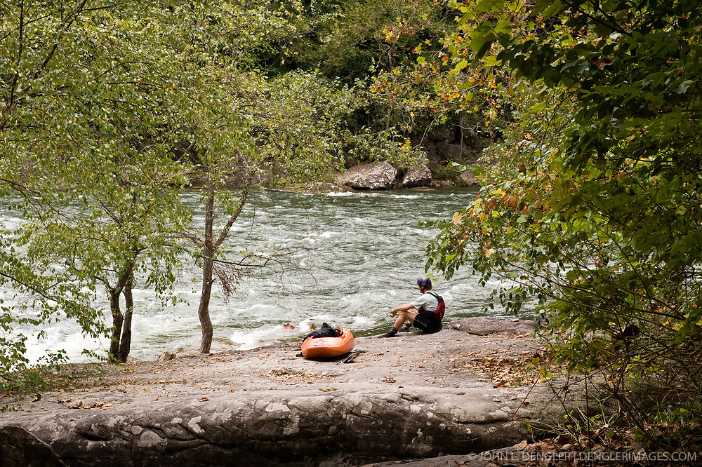 An unidentified whitewater kayaker rests on the bank of the Gauley River near Summersville Dam during American Whitewater's Gauley Fest weekend. The upper Gauley, located in the Gauley River National Recreation Area is considered one of premier whitewater rivers in the country.