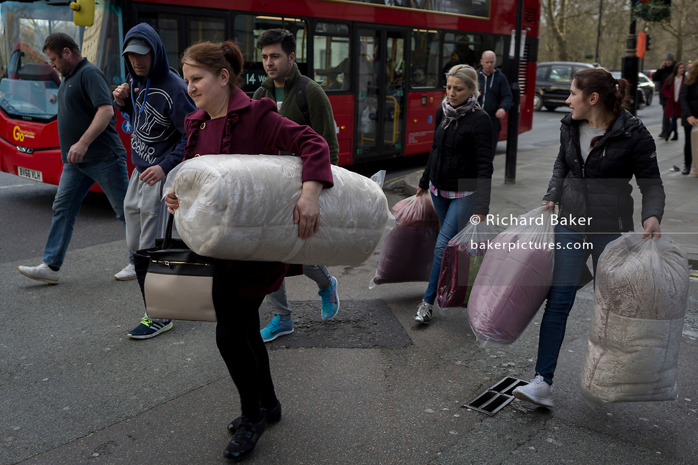Three woman carry soft furnishings sealed in plastic, 21st March 2017, in on Piccadilly, London, England.