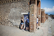 Pompei, Napoli. Un gruppo di turisti scrutano attraverso i fori di un telo bianco di una casa pompeiana chiusa per lavori di restauro;  family inside the archaeological site of Pompeii try with curiosity to be able to see inside of a Roman house under renovation, through the holes of a white towel placed on the door.