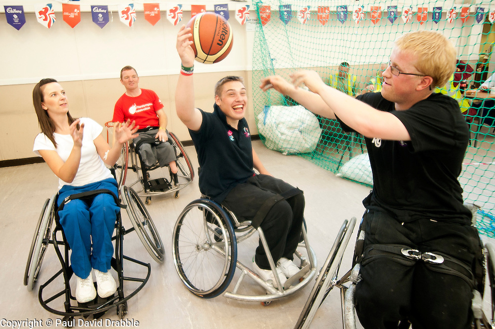 Cadbury 2012 Paralympic demonstration Sheffield..Kraft Lab scientist Kayleigh Jones tries her hand at wheelchair basketball alongside (left to right) coach Andy Atkinson and players Josh Dunn and Mike Porter who were on site with the  RGK Rhinos Sporting club wheelchair basketball team to give Sheffield colleagues an insight into Wheelchair basketball, Paralympic sports and promote awareness around the different sporting disciplines.   .  ....3 September 2012.Image © Paul David Drabble