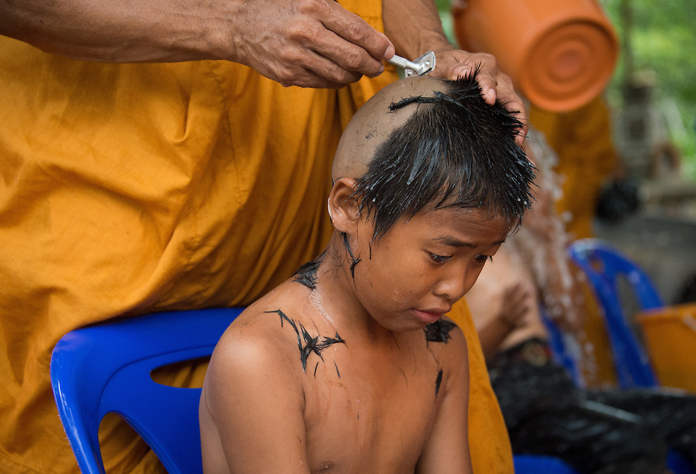 Young men have their heads shaved as they prepare to become novice monks in  rural Nakhon Nayok, Thailand.