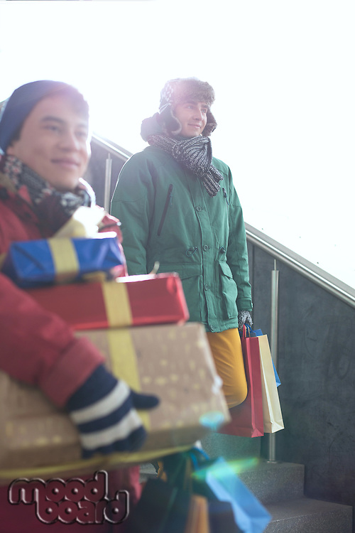 Men with gift boxes and shopping bags standing on steps
