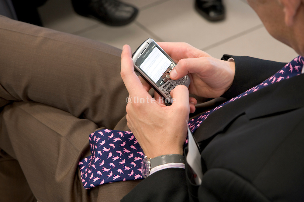 businessman writing a text message while waiting at an airport