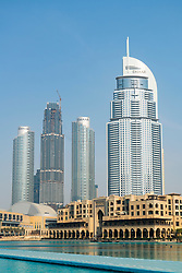 Exterior of the Dubai Mall with new high rise apartment towers under construction to rear in Dubai, United Arab Emirates.