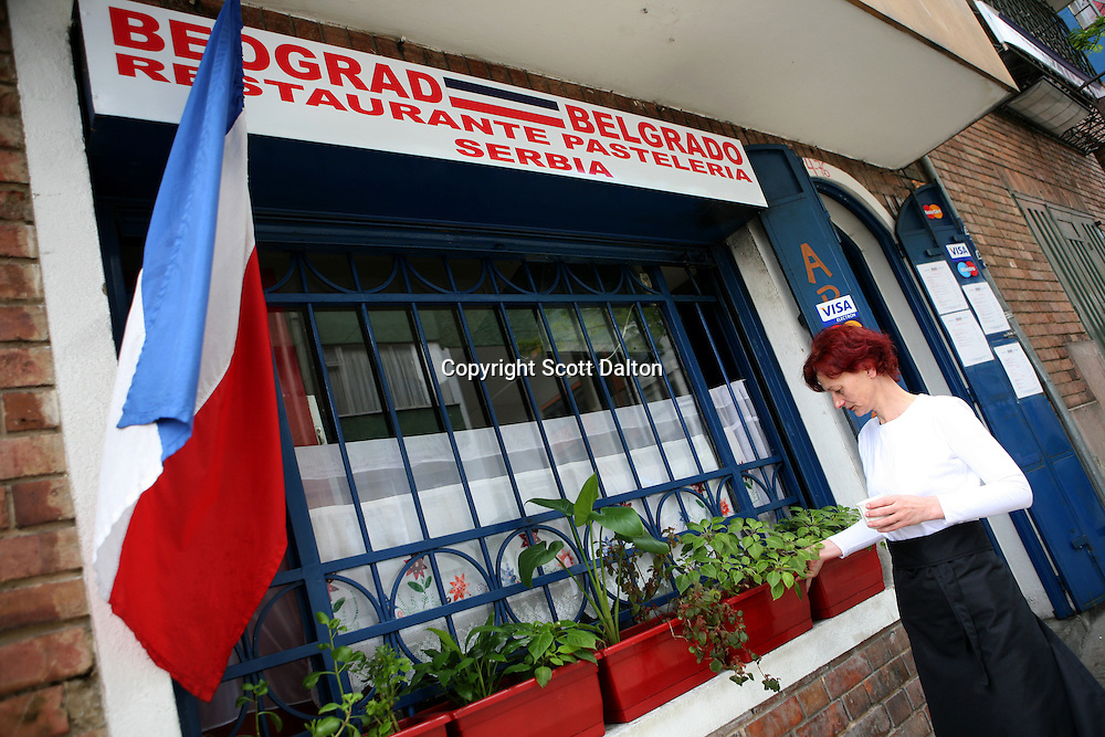 Katarina Markovich, a Serbian war refugee, checks on flowers outside of her restaurant Beograd, located in La Macarena neighborhood in Bogotá, Colombia on Sunday, July 12, 2009. La Macarena has slowly been transforming from a rough neighborhood into a trendy hangout for locals and expats. (Photo/Scott Dalton)