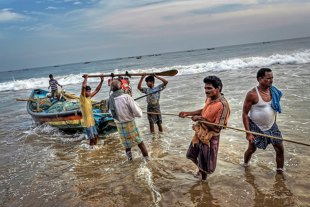 fishermen are releasing a boat into the sea
