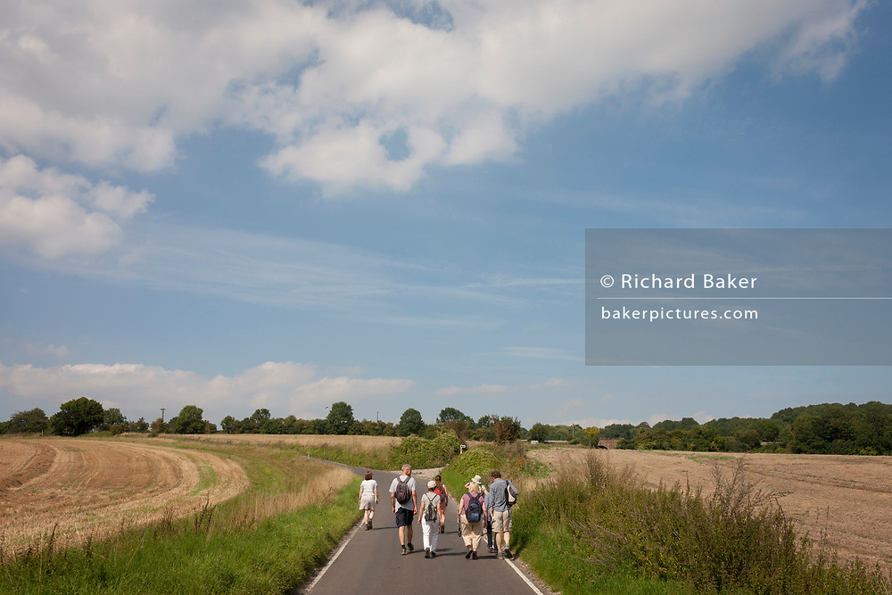 Countryside ramblers walk up a hill on a quiet minor road beneath summer skies, on 27th August 2017, near Cobham, Kent, England.