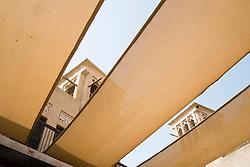 Wind towers seen through cloth sun shades in courtyard of Coin Museum in Al Bastakiya historical district in Bur Dubai United Arab Emirates