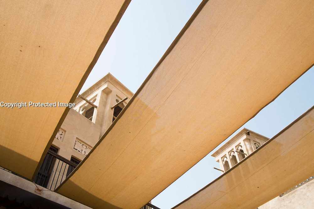 Wind towers seen through cloth sun shades in courtyard of Coin Museum in Al Bastakiya historical district in Bur Dubai United Arab Emirates