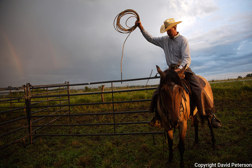As a rainbow appears on the horizon, cowboy Michael Flattery, from Albia, Iowa, prepares his lariat for a cattle roundup at the Bar-B ranch near Albia.  Young calves were roped, branded and vaccinated during the annual event.