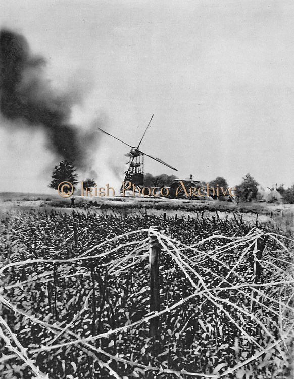 World War I 1914-1918:  Windmill destroyed by German shellfire. Barbed wire defences in foreground.  France World War I. From 'Le Flambeau', Paris, September 1915.