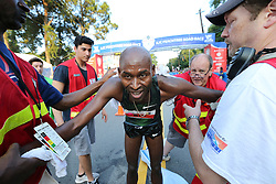 July 4, 2018 - Atlanta, GA, USA - Bernard Kip Lagat is helped to his feet after collapsing to the ground at the finish line to win the AJC Peachtree Road Race with a time of 28:45 in the 10K race on Wednesday, July 4, 2018, in Atlanta. (Credit Image: © Curtis Compton/TNS via ZUMA Wire)