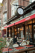 A couple relaxing at an outdoor table at Kalendar, a bistro on College Street in Toronto's Little Italy neighborhood.