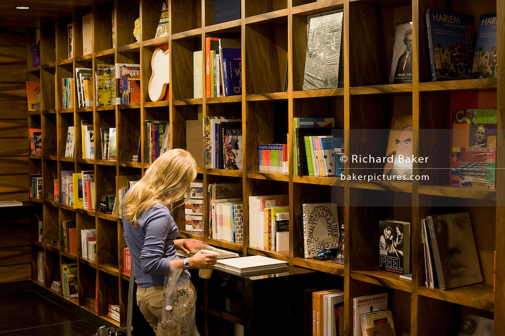 Young lady looks through art books in the Paul Smith shop in Heathrow airport's terminal 5