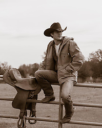 handsome cowboy sitting on a fence at a ranch good looking cowboy sitting on a fence at a ranch