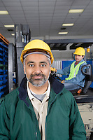 Serious man standing in factory wearing hart hat