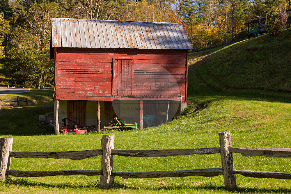A old wooden barn and split rail fence along the Quilt Trails in Prices Creek, North Carolina. The quilt trails honor handmade quilt designs of the rural Appalachian region.
