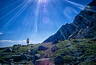 Eric Leroy walks across an alpine meadow in Grand Teton National Park on a climbing expedition.  July 1973.