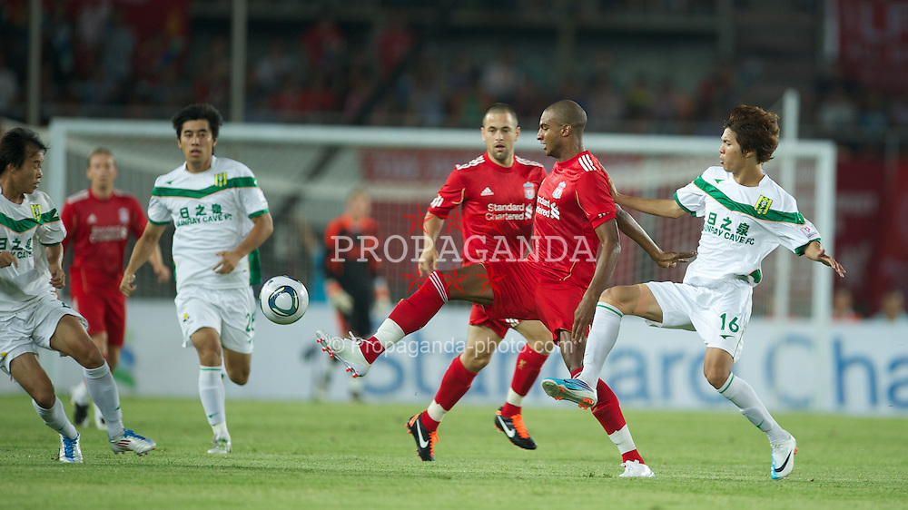 GUANGZHOU, CHINA - Wednesday, July 13, 2011: Liverpool's David Ngog in action against Guangdong Sunray Cave's Li Jian during the first pre-season friendly on day three of the club's Asia Tour at the Tianhe Stadium. (Photo by David Rawcliffe/Propaganda)