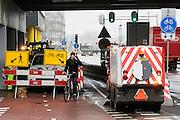 In Utrecht rijden fietsers door de chaos in het stationsgebied. Een veegmachine wacht tot het veilig op het fietspad kan rijden.<br /> <br /> In Utrecht cyclists ride at the chaotic station area. A sweeper wait until it can drive safely on the bike path.