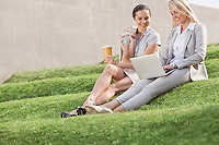 Full length of happy businesswomen looking at laptop while sitting on grass steps against wall