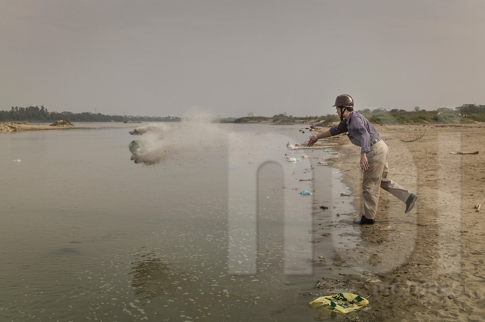 A Vietnamese man throws a plastic bag containing dust and incense ashes into the Red River, Hanoi, Vietnam, Southeast Asia. It is tradition for the ancestor altar to be cleaned the day before Tet.