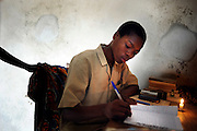 A black teenager does his homework on a table in his bedroom in Cotonou, Benin February 29, 2008.