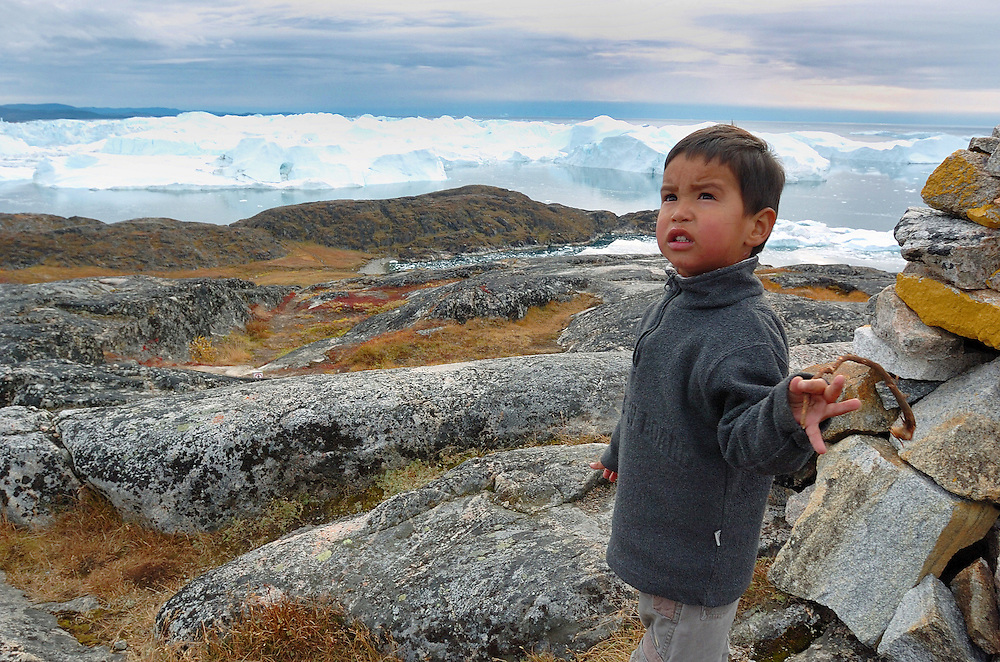 """Kid staring the Ilulissat Icefjord. The Ilulissat Icefjord, a UNESCO World Heritage Site, is located on the west coast of Greenland, 250 km north of the Arctic Circle. It is the sea mouth of Sermeq Kujalleq, one of the few and most productive glaciers through which the Greenland ice cap reaches the sea. Pieces of ice several cubic kilometres in size break offs and travels the Arctic sea, Greenland. Pieces of ice several cubic kilometres in size break offs and travels the Arctic sea, Greenland. Greenland (Greenlandic: Kalaallit Nunaat, meaning """"Land of the Kalaallit (Greenlanders) is a self-governing Danish province located between the Arctic and Atlantic Ocean. A recent study by researchers from NASA's Goddard Space Flight Center shows that Greenland's ice sheet, about 8% of the Earth's grounded ice, is losing ice mass."""