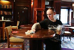 © Licensed to London News Pictures. 04/07/2020. London, UK. A member of staff cleans the table at the THE TOLL GATE, a Wetherspoon pub in north London which reopened on Super Saturday. Cafes, restaurants, pubs and hairdressers across the UK closed on 23 March following the coronavirus lockdown. As restrictions are eased, cafes, restaurants, pubs and hairdressers reopens today. Photo credit: Dinendra Haria/LNP