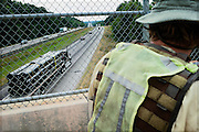 DACULA, GA – JUNE 6, 2014: Unable to walk on the interstates, Karl Bushby walks over a bridge on Highway 124 east of Atlanta.<br /> <br /> Karl Bushby is trying to complete the longest walk in history. Unless the Russians stop him. As a 45 year-old Brit, Bushby been traveling around the world on foot since 1998. In the most recent leg of his journey, Bushby is walking to Washington, D.C. to petition the Russian Embassy to lift a visa ban that prohibited him from continuing his hike through Russia.
