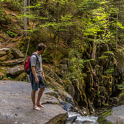 A man explores Screw Auger Falls on Gulf Hagas Brook. Appalachian Trail. Maine's 100 Mile Wilderness.